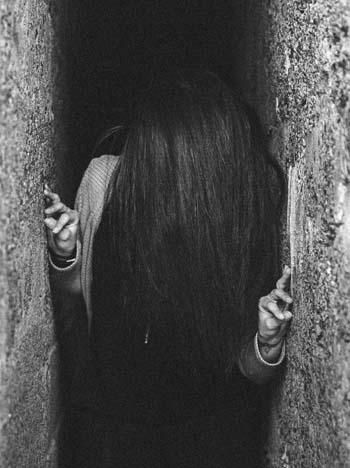 Frau zwischen Wänden