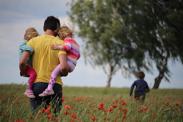 Mann mit Kindern auf einer Wiese